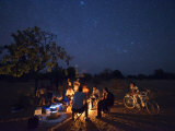 Fire and countless stars illuminate a farmer and his companions Photographic Print by Jim Richardson
