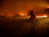 A fireman watches flames advance down a hill toward local businesses Photographic Print by Mark Thiessen