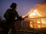 Firefighters spray a boat hauled out of a burning garage Photographic Print by Mark Thiessen