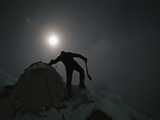 A mountain climber shakes snow from a tent on Nanga Parbat Photographic Print by Tommy Heinrich