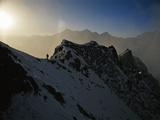 Climber on a steep ridge of Nanga Parbat with the sun guiding his way Photographic Print by Tommy Heinrich