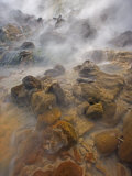 Steaming water flows over rocks stained by algae and bacteria Photographic Print by Michael Melford