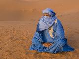 Veiled Tuareg Man Sitting Cross-Legged on the Sand, Erg Chebbi, Morocco Fotografisk tryk