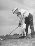 Father Teaching His Small Son How to Play Golf Fotografická reprodukce