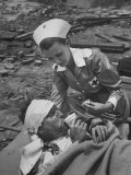 The Red Cross Nurse Trying to Help the Injured Man Eat and Drink Lmina fotogrfica de primera calidad por Allan Grant