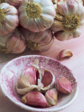 Close-Up of Cloves of Garlic in a Pink Bowl, with a Bunch of Heads of Garlic in the Background Photographic Print by Michelle Garrett
