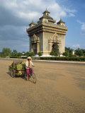 Woman on a Bicycle Rides Past the Anousavari Monument in Vientiane, Laos, Southeast Asia Photographic Print by Mcleod Rob