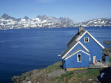 Blue Painted Wooden House on the Coast, with Mountains in the Background, Ammassalik, Greenland Photographic Print by Lomax David