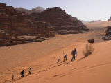 Young People Climbing a Red Sand Dune with Rocks in Background, Wadi Rum, Jordan, Middle East Photographic Print by Simanor Eitan