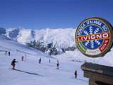 Sign with Skiers and Mountains in the Background at the Ski Resort of Livigno in Northern Italy Photographic Print by Teegan Tom