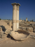 Stone Pithos in the Palaestra with Temple of Apollo in the Ruins of Kourion, South Cyprus Photographic Print by Teegan Tom