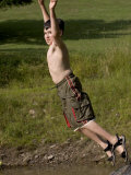 9 Year Old Boy Jumping Off a Rock into a Pond, Woodstock, New York, USA Photographic Print by Paul Sutton