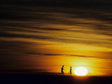 Couple Running at Sunset Photographic Print