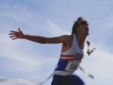 Male Runner Victorious at the Finish Line in a Track Race Photographic Print