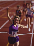 Female Runner Victorious at the Finish Line in a Track Race Photographie