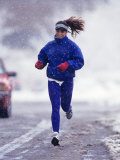 Woman Running During a Snow Storm Photographic Print