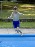 9 Year Old Boy Jumping into the Swimming Pool, Kiamesha Lake, New York, USA Photographic Print by Paul Sutton