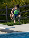 5 Year Old Girl Jumping Off Diving Board into Swimming Pool, Woodstock, New York, USA Photographic Print by Paul Sutton