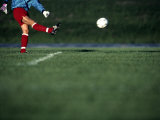 Male Soccer Player Kicking a Soccer Ball Photographic Print by Steven Sutton