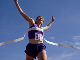 Female Runner Celebrates Victory at the Finish Line Photographic Print