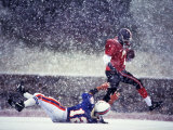 Football Players in Action During Snowy Game Photographic Print