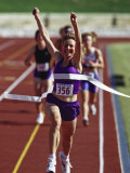 Female Runner Victorious at the Finish Line in a Track Race Photographic Print