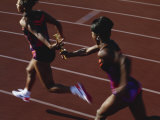 Female Runner Competing in a Relay Track Race Photographic Print