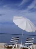 Relaxing Beach Chairs and Umbrella Await Customers Photographic Print by Paul Sutherland