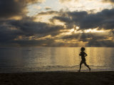 Silhouetted Woman Jogging on a Beach at Twilight Photographic Print by Mattias Klum