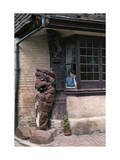 Woman Peers Out of a 16th Century Inn, Next to a Lion Figurehead Photographic Print by Clifton R. Adams