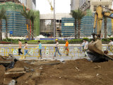 Pedestrians and Workers Walk Past a Hotel Construction Site in Macao Photographic Print by  xPacifica