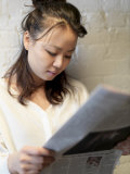 Close-up View of a Young Asian Woman Reading a Paper Photographic Print by  xPacifica