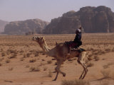 Young Bedouin Races His Camel Below Huge Towers in Arabian Desert Photographic Print by Gordon Wiltsie
