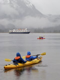 Kayaking in Khutze Inlet Near a Cruise Ship Photographic Print by Michael Melford