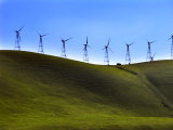 Vehicle Dwarfed by Looming Wind Turbines as it Drives Along a Ridge Photographic Print by White & Petteway
