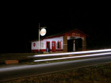 Restored Antique Gas Station Glows in the Night as Cars Pass By Photographic Print by  White & Petteway