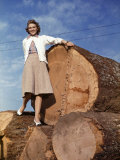 Woman Stands on a Pile of Gigantic Douglas Fir Logs Photographic Print by Maynard Owen Williams
