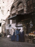 Man and Two Women Stand at His Home-Grown Fruit Booth in Cairo Photographic Print by Gervais Courtellemont