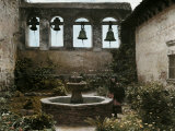 Woman Stands Next to a Fountain in Mission of San Juan Capistrano Fotografisk trykk av Charles Martin