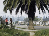 Two Girls Chat on a Street with Oil Derricks in the Background Photographic Print by B. Anthony Stewart