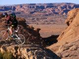 Woman Mountain Biking on Desert Cliffs Photographic Print by Kate Thompson