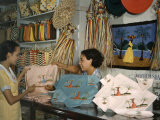 Shopkeeper at an Arts Co-Op Shows a Customer Embroidered Linens Photographic Print by Edwin L. Wisherd