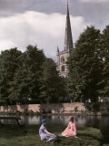 Two Women Sit Near the Avon River with the Holy Trinity Church Behind Photographic Print by Clifton R. Adams