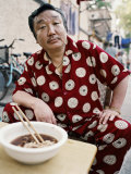 Man in Silk Pajamas Eats a Bowl of Noodles on the Street Photographic Print by  xPacifica
