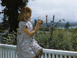 As Girl Fills One Bird Feeder Vial, a Hummingbird Sips from Another Photographic Print by Edwin L. Wisherd