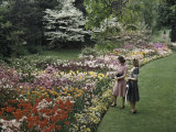 Two Women Admire Tulips in a Garden Photographic Print by Charles Martin