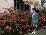 Young Woman Stands by a Garden Full of Poinsettias Beside a House Photographic Print by Clifton R. Adams