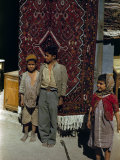 Children Stand Beside Persian Rug Hanging at a Storefront's Entrance Photographic Print by Maynard Owen Williams