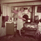 Woman Stands at Old-Fashioned Stove to Cook, Cats Prowl at Her Feet Photographic Print by Justin Locke