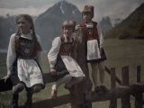 Three Norwegian Girls in Traditional Dress Linger on a Fence Photographic Print by Gustav Heurlin